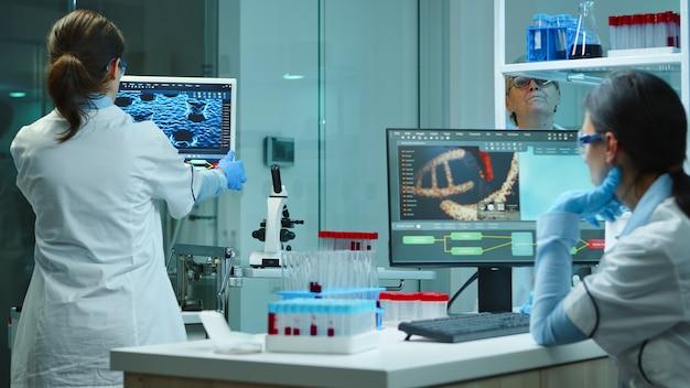 Colegas de trabalho de cientistas trabalhando em horas extras de laboratório químico moderno equipado. material de médicos examinando a evolução da vacina usando alta tecnologia e pesquisa de tratamento contra o vírus covid19