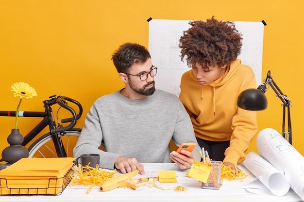 Colegas de trabalho de raça mista, mulher e homem, tentam encontrar solução de informações de verificação de trabalho na internet por meio de papéis de estudo de celular posam em espaço de coworking
