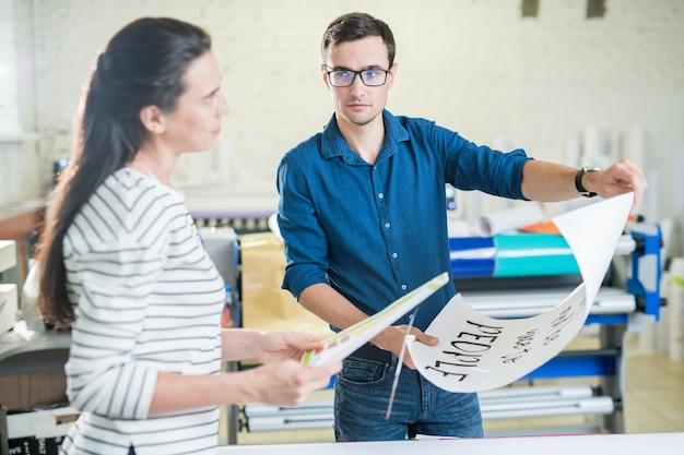 Colegas de trabalho de tipografia discutindo cartaz