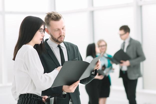 Colegas de trabalho discutem documentos de negócios em pé no escritório