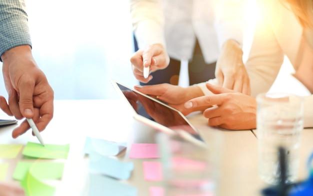 Colegas de trabalho discutindo a situação financeira de seus negócios em um tablet digital