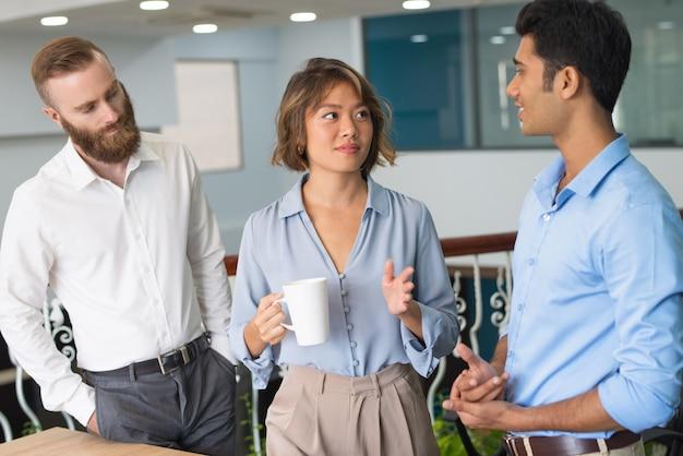 Colegas de trabalho, discutindo o trabalho durante a pausa para o café
