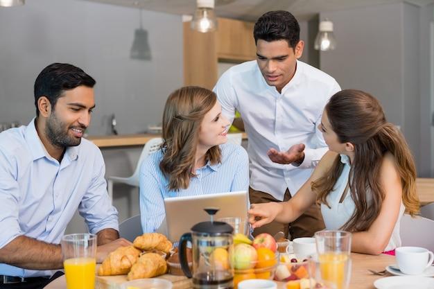 Colegas de trabalho discutindo sobre tablet digital enquanto tomam café da manhã