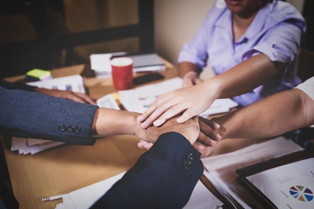 Colegas de trabalho em equipe, juntando as mãos em toda a mesa de reunião
