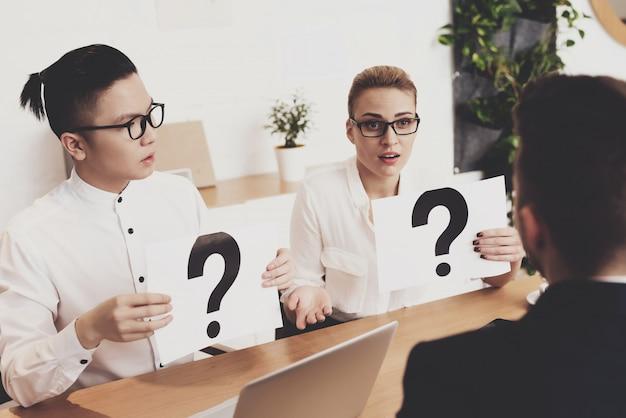 Colegas de trabalho estão segurando pontos de interrogação no trabalho
