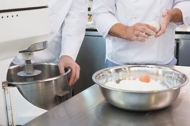Colegas de trabalho fazendo massa com ovos e farinha na cozinha da padaria