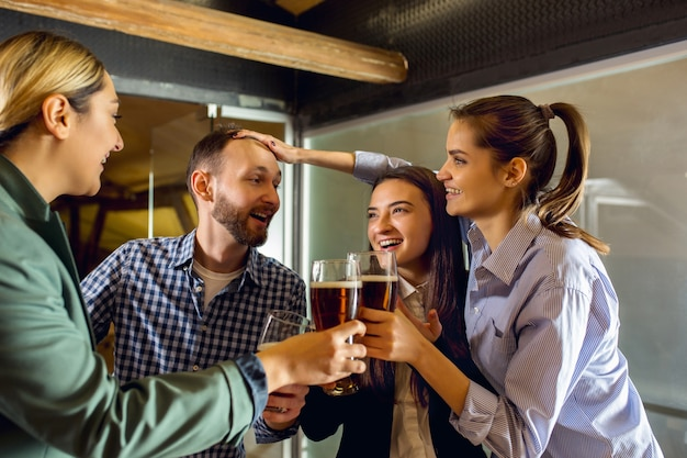 Colegas de trabalho felizes comemorando evento corporativo após um dia tenso de trabalho