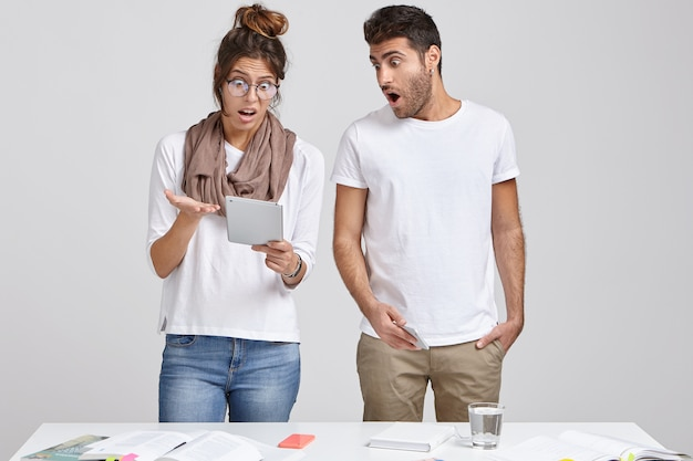 Colegas de trabalho femininas e masculinas terríveis e surpresas olham com expressão estupefata para o bloco de notas, recebem comentários e observações ruins sobre seu trabalho de projeto, ficam perto da parede branca perto da mesa