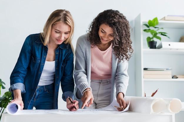 Colegas de trabalho femininas, inclinando-se sobre o desenho de planta de papel
