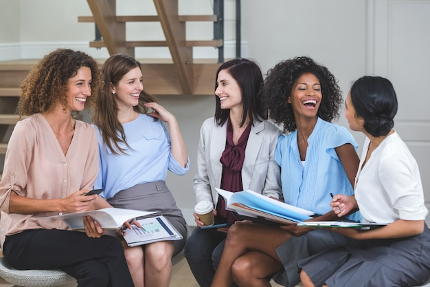 Colegas de trabalho feminino interagindo uns com os outros