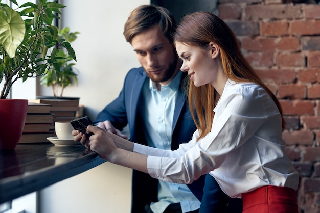 Colegas de trabalho, homem e mulher, sentados em um café com comunicação por telefone