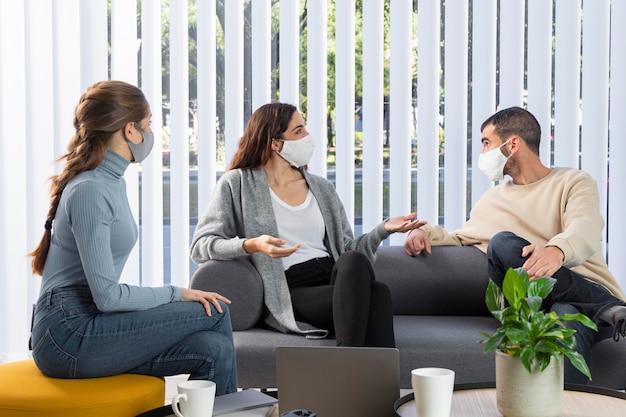 Colegas de trabalho medianas no sofá com máscaras