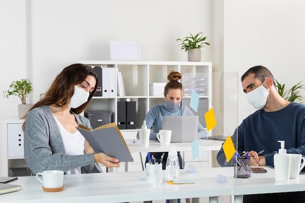 Colegas de trabalho mediano usando máscaras