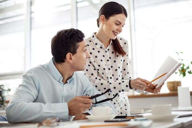 Colegas de trabalho. mulher jovem e bonita, de cabelos escuros, sorrindo e mostrando seu caderno para um homem sentado à mesa de óculos