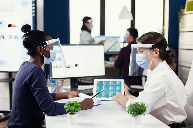 Colegas de trabalho multiétnicas analisando gráfico financeiro durante covid19. grupo diversificado de empresários trabalhando e se comunicando em escritórios criativos com novas normais, respeitando a distância social.