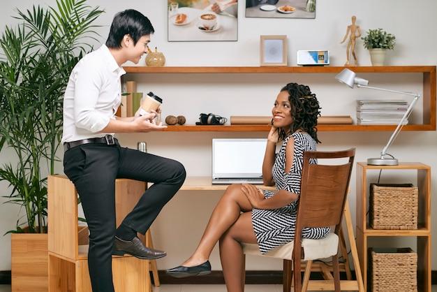 Colegas de trabalho multiétnicas positivas no intervalo para o café e discutindo notícias e fofocas
