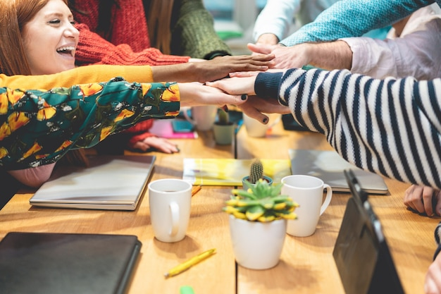 Colegas de trabalho multirraciais felizes dando motivação de força - foco nas mãos