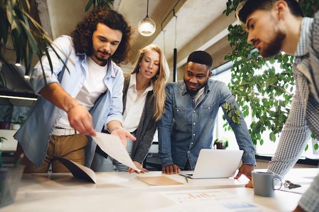 Colegas de trabalho multirraciais sorridentes trabalhando juntos em uma reunião de escritório discutem