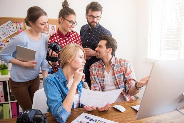 Colegas de trabalho no escritório com câmeras fotográficas e um computador