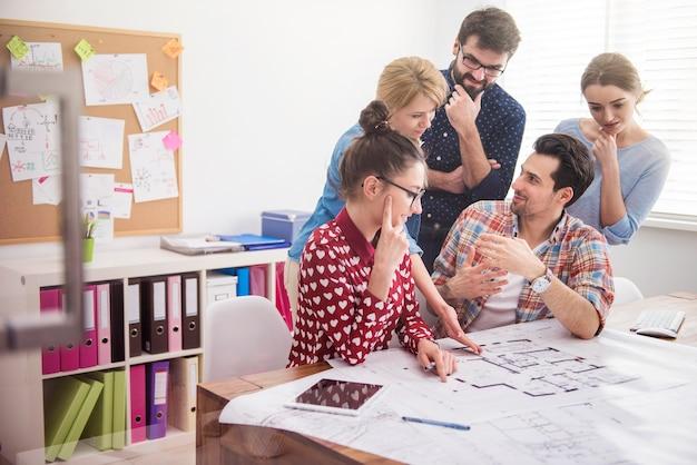 Colegas de trabalho no escritório com planos de arquitetura e um computador