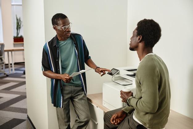 Colegas de trabalho perto da impressora do escritório fazendo cópias de documentos e discutindo o desenvolvimento do projeto