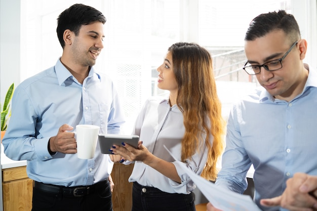 Colegas de trabalho positivos com tablet animado com discussão