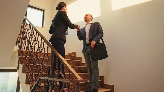 Colegas de trabalho, reunidos na escada em uma empresa corporativa de finanças, apertando as mãos. equipe de empresários profissionais trabalhando juntos no moderno edifício financeiro, cumprimentando e conversando entre si.