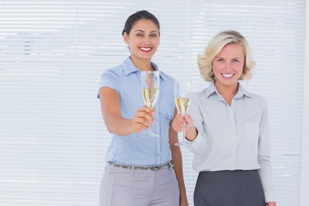 Colegas de trabalho segurando flautas de champanhe