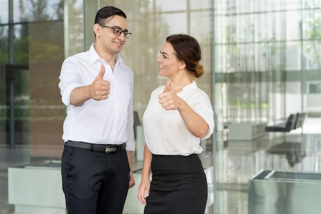 Colegas de trabalho sorridentes olhando uns aos outros e expressando aprovação