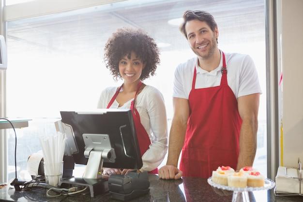 Colegas de trabalho sorridentes posando juntos atrás do balcão