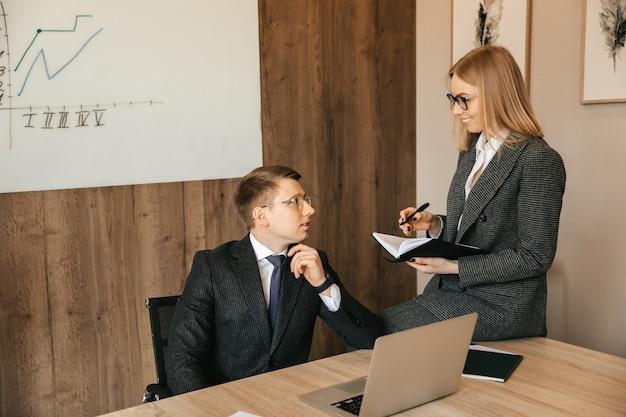 Colegas de trabalho trabalham juntos. uma equipe de dois empresários sorridentes está conversando e olhando documentos. a empresária escreve em um caderno.