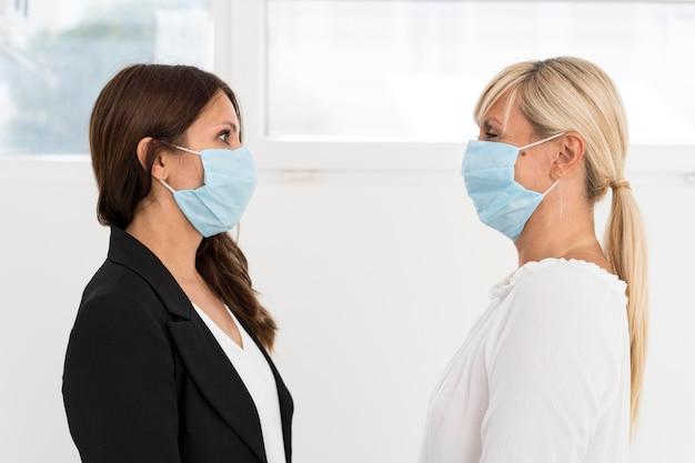Colegas de trabalho usando máscara de proteção no trabalho