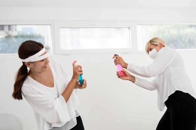 Colegas de trabalho usando proteção facial e brincando com desinfetante para as mãos