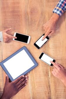 Colegas de trabalho usando tecnologias na mesa no escritório