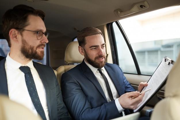 Colegas discutindo contrato no carro