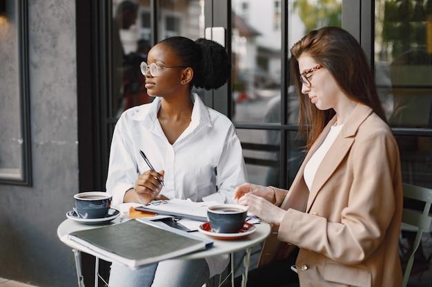 Colegas discutindo dados no café ao ar livre. multirraciais femininas analisando estratégia produtiva para projetos de negócios usando documentos em lanchonete