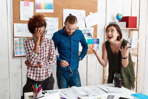 Colegas discutindo, discutindo desenhos, novas idéias no escritório