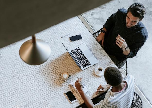 Colegas discutindo seu trabalho em um laptop