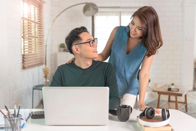 Colegas do jovem casal asiático alegre trabalham com o computador laptop dentro de casa, no escritório, conversando entre si.