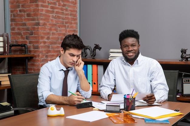 Colegas do processo de trabalho da equipe de visão frontal tendo negociações comerciais no escritório