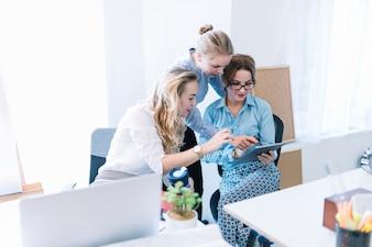 Colegas do sexo feminino apontando e olhando para tablet digital no escritório