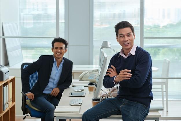 Colegas do sexo masculino no escritório espaçoso, olhando para a câmera alegremente