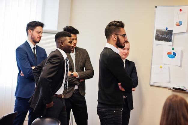 Colegas do sexo masculino que trabalham em equipe cooperam, equipe multirracial de funcionários concentrada no planejamento do projeto contra a diretoria e na discussão de idéias.
