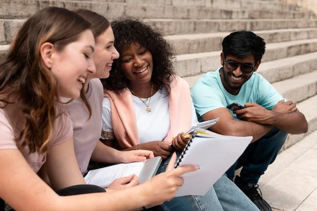 Colegas estudando juntos na frente de sua faculdade