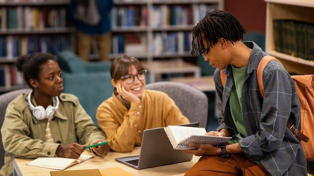 Colegas estudando na biblioteca da universidade
