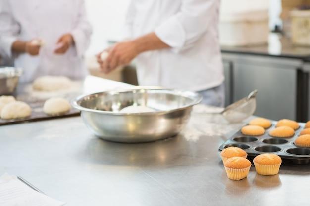 Colegas fazendo bolinhos na bancada na cozinha da padaria