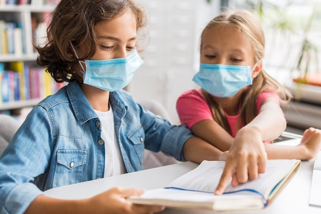 Colegas fazendo sua lição de casa usando uma máscara facial