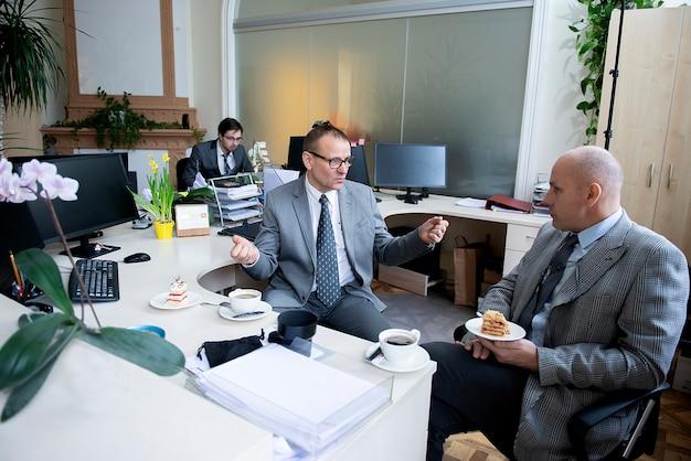Colegas fazendo uma pausa para o café no escritório em sua mesa de trabalho Foto Premium