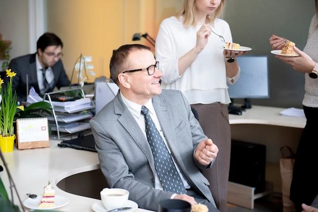 Colegas fazendo uma pausa para o café no escritório em sua mesa de trabalho