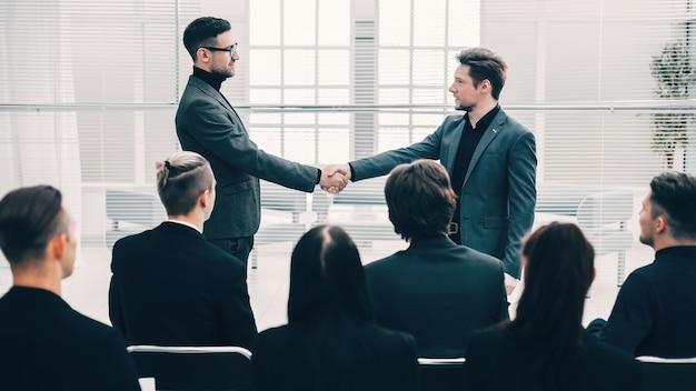 Colegas felizes, apertando as mãos uns dos outros. reuniões e parcerias